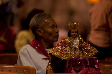 Devotees Holding The Statue Of Santo Nino